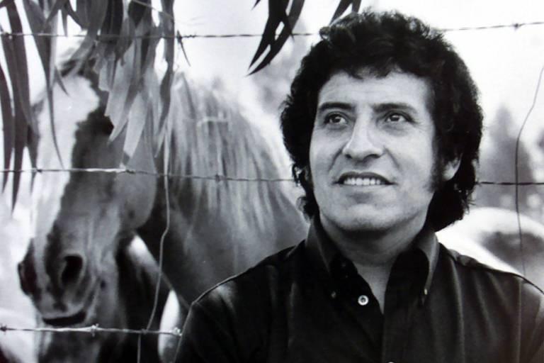 o cantor victor jara está em frente a um cavalo nesta foto em preto e branco