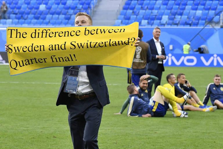 """O jogador Sebastian Larsson, da Suécia, mostra faixa aos torcedores após a seleção de seu país se classificar contra a Suíça: """"A diferença entre Suíça e Suécia? Quartas de final"""""""