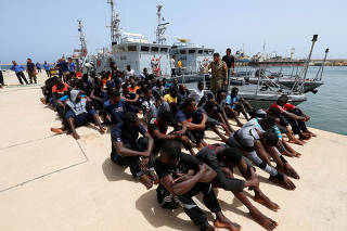 Migrants sit at a naval base after being rescued by Libyan coast guards in Tripoli