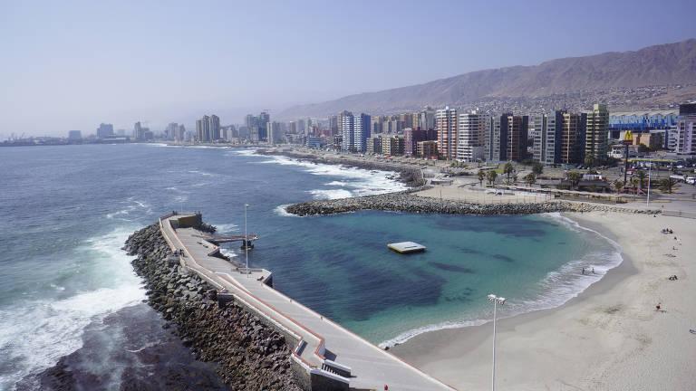 Praia com águas claras com prédios e, ao fundo, uma montanha