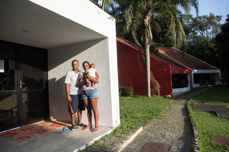 Gilberto e Yulexis carregam uma criança de colo. Eles estão parados ao lado da varanda de um prédio baixo; ao fundo à direita deles, duas palmeiras e duas casas: uma vermelha e outra branca com telhado marrom
