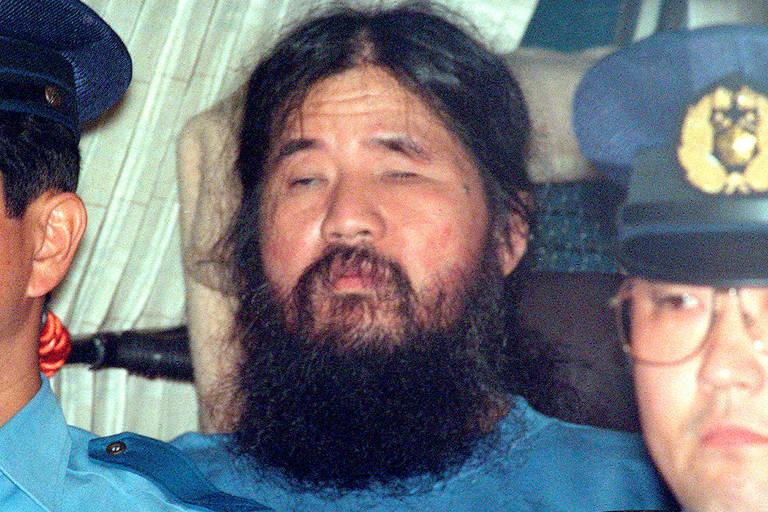 Shoko Asahara aparece no centro da imagem, com barba crescida, cabelo grande preso e uniforme azul escuro. À frente dele, estão dois policiais, cujos rostos aparecem parcialmente na imagem.