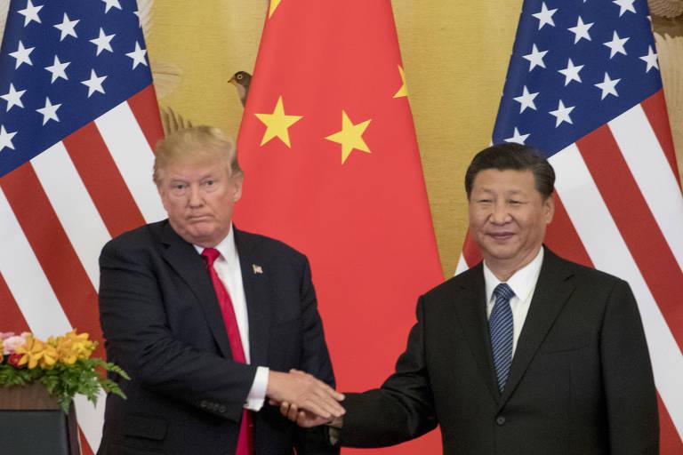 O presidente dos EUA, Donald Trump, e o presidente chinês Xi Jinping se cumprimentam durante encontro em Pequim em maio