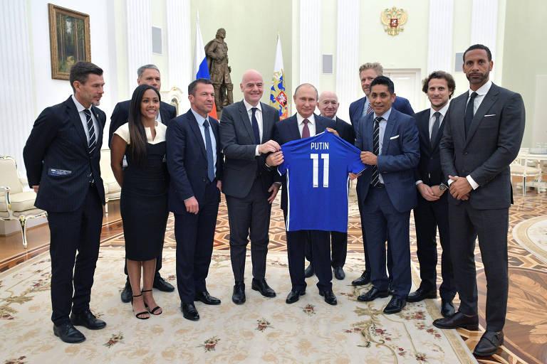 Presidente russo Vladimir Putin posa com camisa de futebol durante reunião com ex-jogadores de futebol e autoridades, liderada pelo presidente da Fifa, Gianni Infantino, no Kremlin, em Moscou