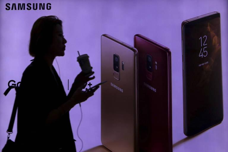 Mulher em frente a um anúncio do Galaxy S9, da Samsung; gigante sul-coreana espera declínio trimestral nos lucros devido à fraca demanda por chips de memória e gastos maiores com o marketing de smartphones