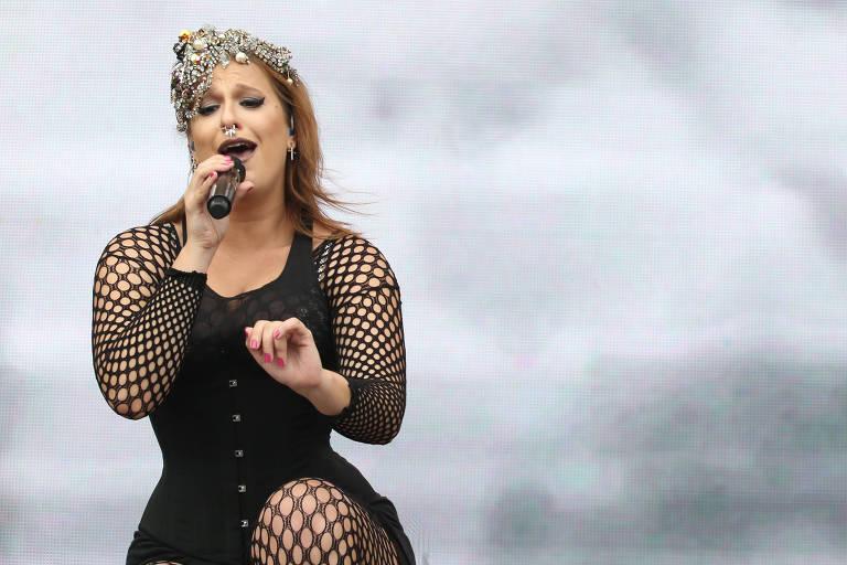 Enquanto canta num palco, Alice segura o microfone com a mão direita e veste roupa preta