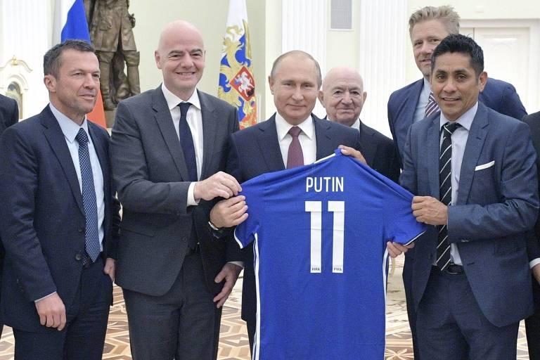 Putin segura uma camiseta azul de futebol com seu nome e o número 11. Ao lado esquerdo dele está Infantino.