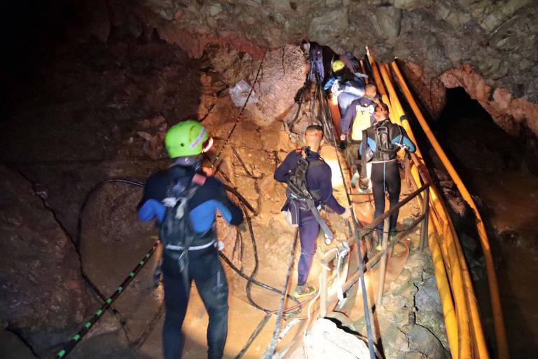 Membros da equipe de resgate tailandeses caminham dentro de uma caverna onde 12 garotos e seu treinador de futebol estão presos desde 23 de junho na Tailândia