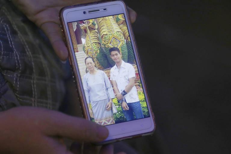 A tia de Ekapol Chantawong mostra uma foto no celular do treinador ao lado de sua avó