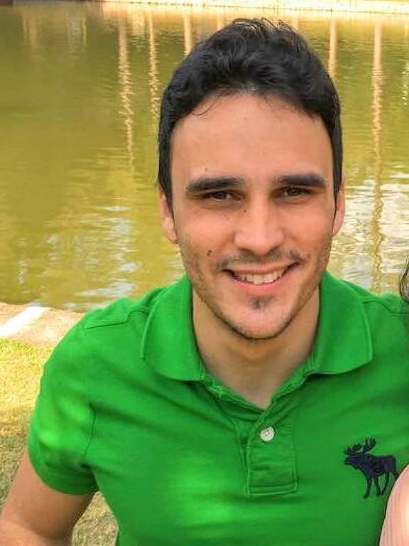 Rafael Garcia, 27, está sentado à frente de um lago de camisa polo verde