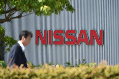 (FILES) This file photo taken on May 11, 2017 shows a man walking in front of the logo of Japan's Nissan Motor Corporation at its global headquarters in Yokohama, Kanagawa prefecture. Nissan said on July 9, 2018 it had found falsification of data on emissions and fuel efficiency for cars made at almost all its plants in Japan. / AFP PHOTO / Kazuhiro NOGI