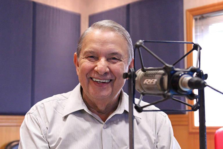 José Paulo de Andrade veste camisa social e sorri largamente. Ele está em um estúdio e tem um microfone profissional à sua frente