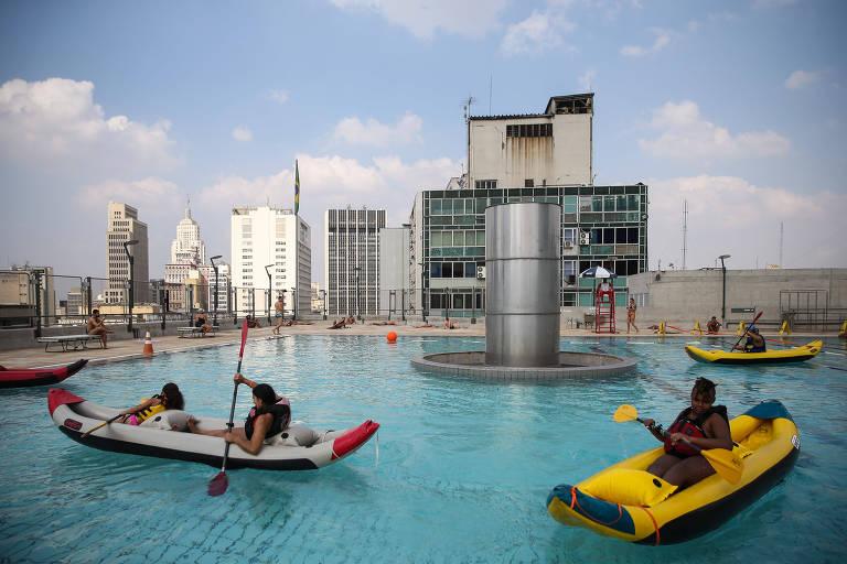 Paulistanos aproveitam dia de sol em São Paulo para terem aulas de caiaque no Sesc 24 de Maio; na foto, dois caiaques infláveis são conduzidos por pessoas dentro de uma piscina no alto de um prédio no centro de São Paulo. Ao fundo, estão prédios do centro da cidade.