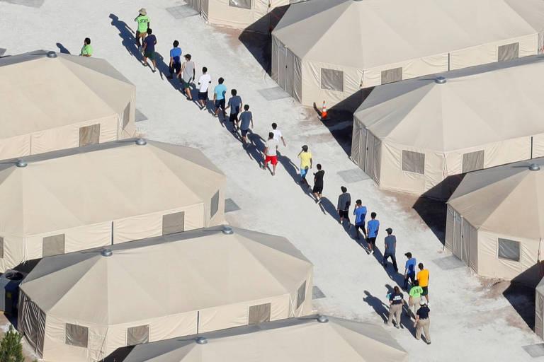 Doze meninos perfilam entre agentes de imigração, que estão em duplas nas duas pontas da fila. Eles formam em um corredor entre barracas feitas de lona bege.
