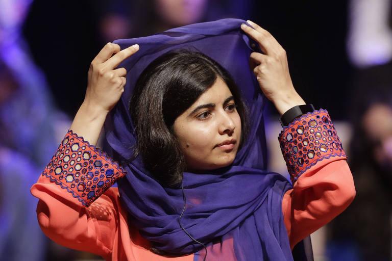 Malala levanta seu véu islâmico roxo. Ela usa uma túnica laranja com detalhes nas mangas em laranja e roxo.