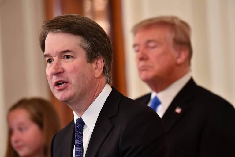 De terno preto, camisa branca e gravata azul marinho, Kavanaugh aparece de perfil falando. Ao fundo, desfocados, estão Trump à direita e uma das filhas do juiz à esquerda.