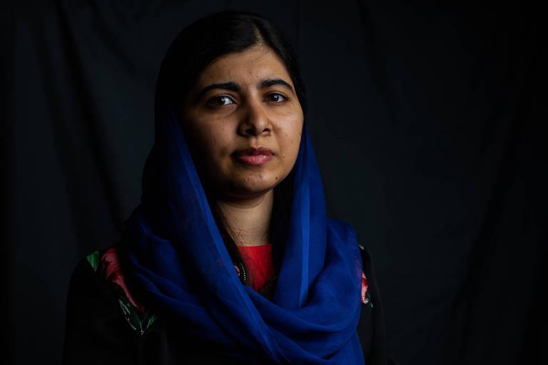 Malala aparece do peito para cima, com lenço azul e vestido laranja. Ela está em um local com fundo preto.