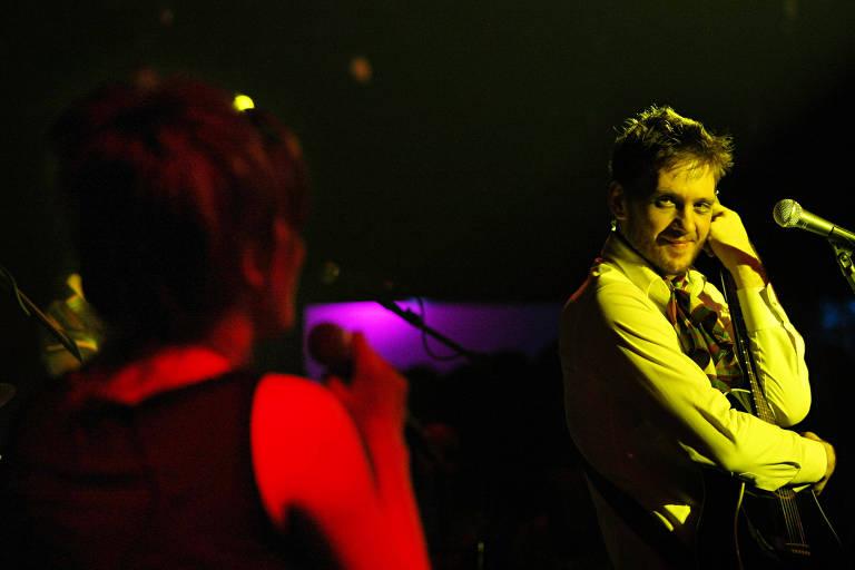 No palco, o cantor André Frateschi sorri enquanto olha para outro integrante da banda que está de costas