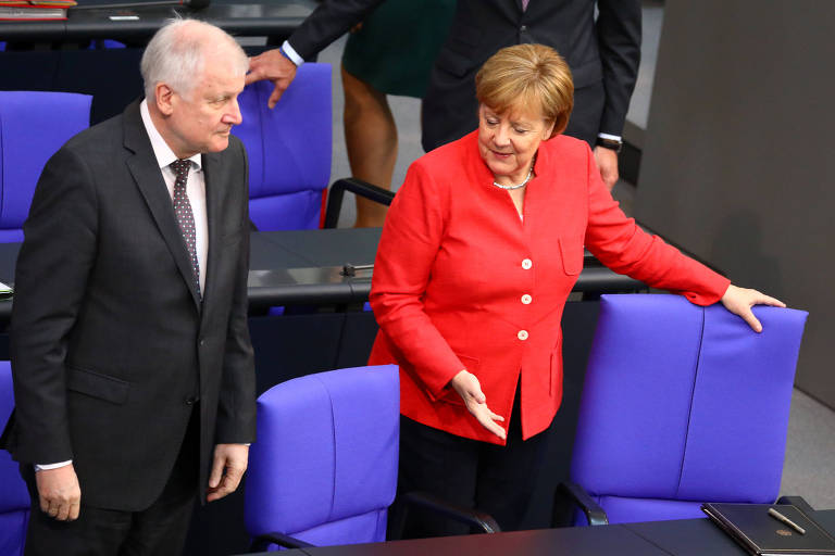 Com blazer vermelho e calça preta, Merkel aponta para uma das poltronas roxas do Parlamento alemão enquanto conversa com Seehofer
