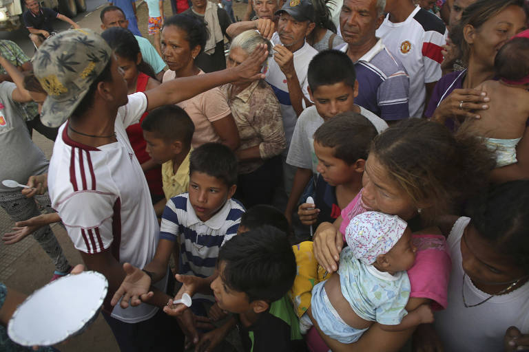 De camisa branca com detalhes em vermelho, homem tenta organizar grupo de cerca de 20 pessoas, incluindo mulheres com crianças de colo, que tentam receber uma quentinha. A cena é vista do alto.