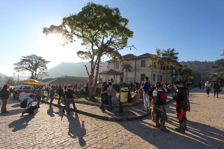 Pessoas caminham por praça em Paranapiacaba. Ao fundo, há um sobrado histórico. A praça é cercada por ruas de paralelepípedo