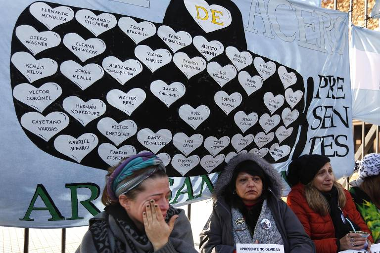"""Três mulheres aparecem na imagem. A primeira à esquerda seca lágrimas, a do meio carrega um cartaz em papel sulfite com a mensagem pedindo para encontrar a embarcação, e a terceira segura uma cuia de mate. Ao fundo delas, está um cartaz, com a mensagem """"ARA San Juan Presente"""" com um desenho do submarino com os nomes dos 44 tripulantes em corações."""