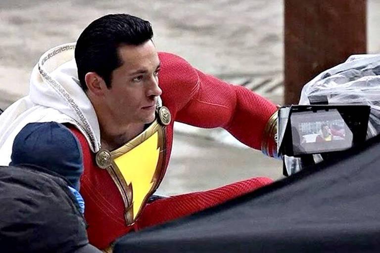 Zachary Levi com os trajes do herói Shazam