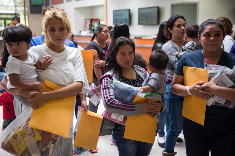 Quatro mulheres carregam seus filhos de colo e envelopes pardos com documentos.
