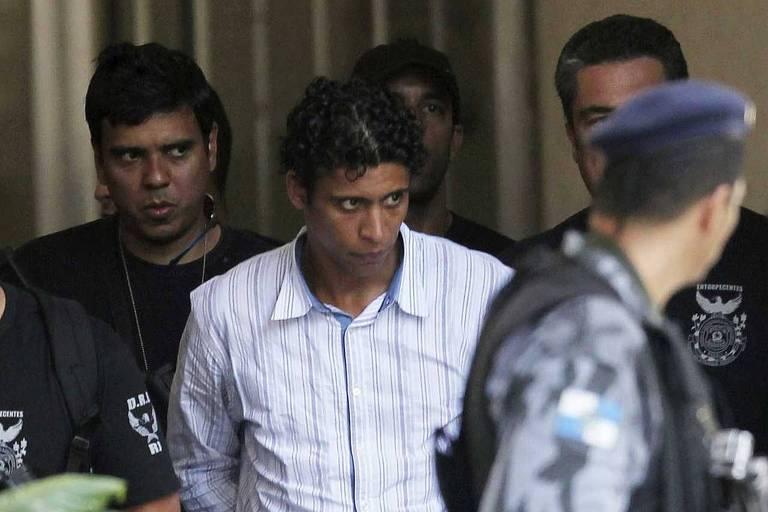 Antônio Bonfim Lopes, conhecido como Nem, é escoltado por políciais ao chegar na sede da polícial federal, no Rio de Janeiro, em 2011