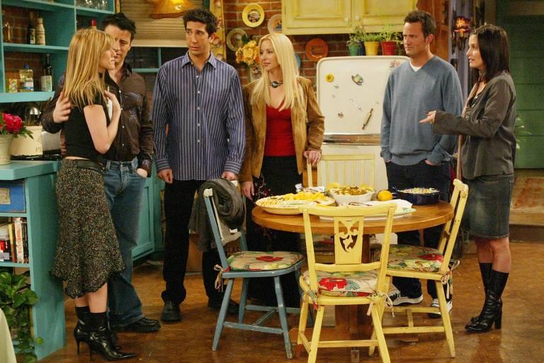 Os seis amigos juntos na cozinha do apartamento de Monica (Courtney Cox Arquette). Todos olham para Rachel (Jennifer Aniston) e parecem tentar consolá-la