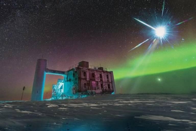 Aurora boreal ao fundo de um telescópio