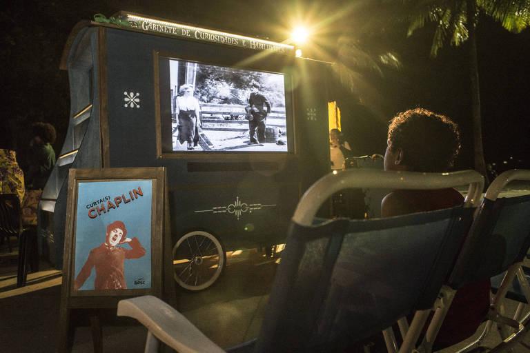 Criança sentada assiste curta de Chaplin