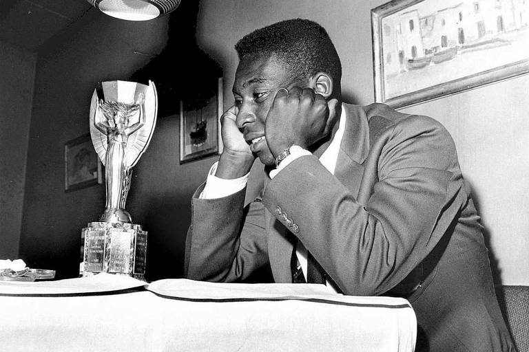 Pelé observa a taça Jules Rimet, conquistada pela primeira vez pelo Brasil em 1958
