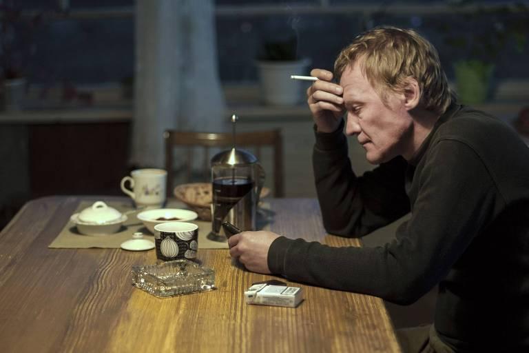 homem com cigarro, pensativo, em mesa de madeira