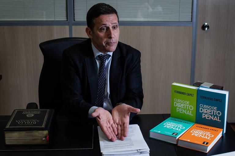 O deputado estadual Fernando Capez (PSDB), ex-presidente da Assembleia Legislativa de São Paulo, em seu gabinete. Ele está sentado em sua mesa, apoiando as duas mãos sobre o processo contra ele no caso da máfia da merenda. À direita, vê-se edições de seus livros sobre direito penal. À esquerda, uma edição da Bíblia