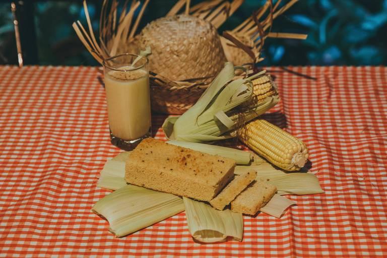 Mosca com toalha xadrez branca e vermelha tem um copo de suco de milho, um bolo de milho, além de espigas de milho e um chapéu de palha enfeitando