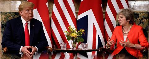 TOPSHOT - US President Donald Trump listens to (L) Britain's Prime Minister Theresa May prior to a meeting at Chequers, the prime minister's country residence, near Ellesborough, northwest of London on July 13, 2018 on the second day of Trump's UK visit. US President Donald Trump launched an extraordinary attack on Prime Minister Theresa May's Brexit strategy, plunging the transatlantic