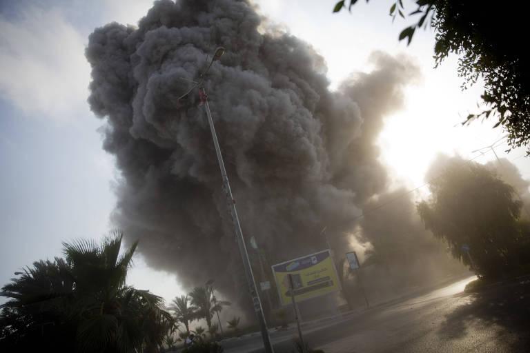 Fumaça sobe depois que ataque aéreo israelense atingir prédio governamental em Gaza no sábado (14)