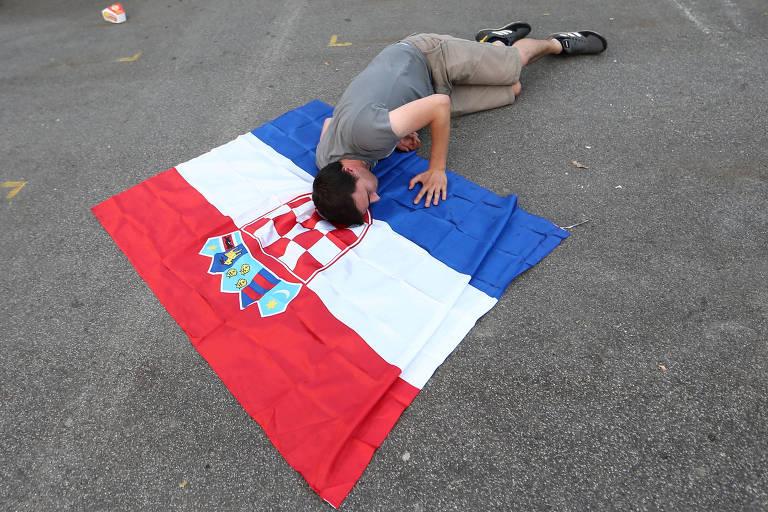 Torcedor croata em Zagreb beija sua bandeira depois da derrota da sua seleção