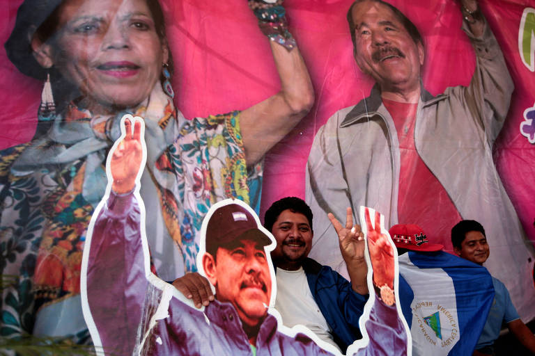"""A man stands with images of Nicaragua's President Daniel Ortega and Vice President and First Lady Rosario Murillo during celebrations to mark the 39th anniversary of the """"Repliegue"""" (Withdrawal) in Masaya"""