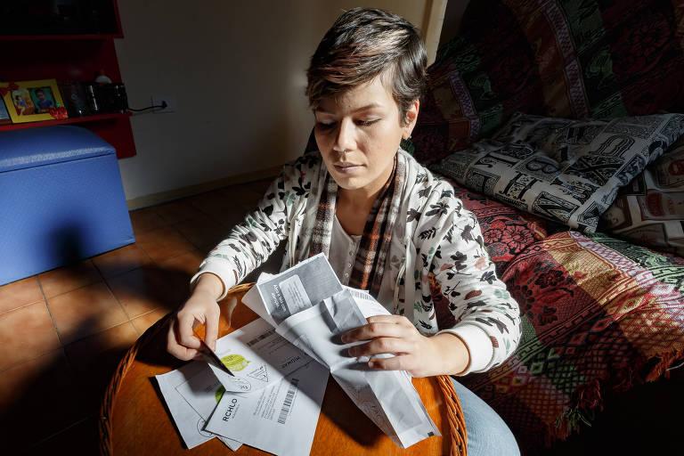 Sayuri Hamada em sua casa mexe em faturas de cartão de crédito
