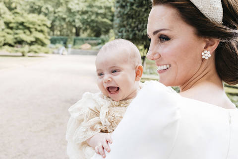 In this Monday, July 9, 2018 photo made available by Kensington Palace, Kate, the Duchess of Cambridge poses for a photo with Prince Louis in the garden of Clarence House, following Prince Louis's baptism at the Chapel Royal, St. James's Palace, in London. (Matt Porteous/Kensington Palace via AP) ORG XMIT: AMB803