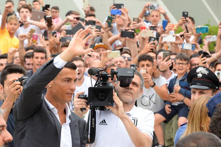 O português Cristiano Ronaldo saúda os torcedores da Juventus em sua chegada ao Aeroporto de Turim, nesta segunda-feira (16)
