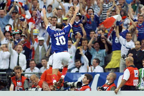 (FILES) In this file photo taken on July 12, 1998 French Zinedine Zidane jumps over the barrier as he celebrates after scoring the first goal for his team at the Stade de France in Saint-Denis, during the 1998 World Cup final match between Brazil and France.  / AFP PHOTO / Patrick HERTZOG ORG XMIT: SDF95