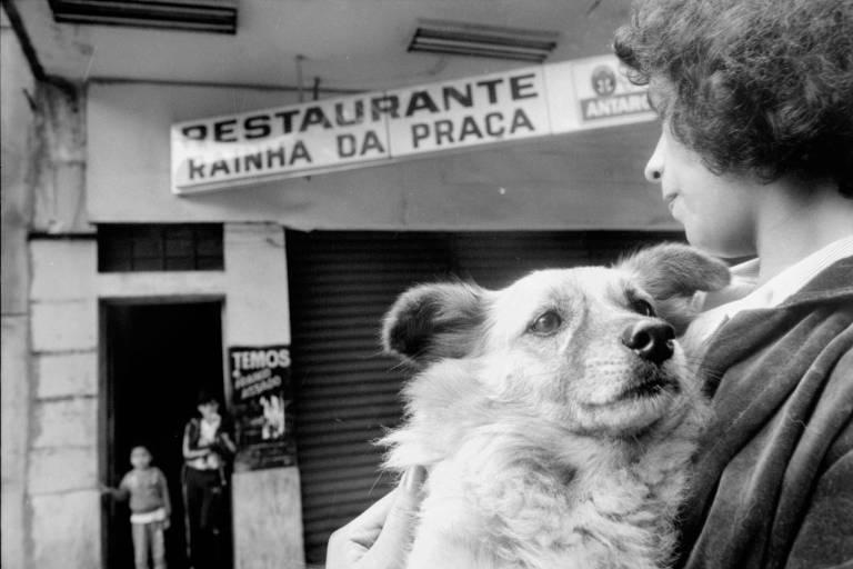 """Mulher segura cachorro em frente ao restaurante """"Rainha da Praça"""", em Santos (SP)"""