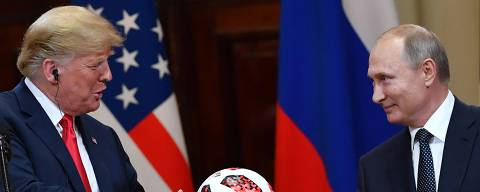 Russia's President Vladimir Putin (R) offers a ball of the 2018 football World Cup to US President Donald Trump during a joint press conference after a meeting at the Presidential Palace in Helsinki, on July 16, 2018. The US and Russian leaders opened an historic summit in Helsinki, with Donald Trump promising an