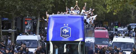 France's Raphael Varane holds the trophy as he celebrates with teammates on the roof of a bus while parading down the Champs-Elysee avenue, in Paris, Monday, July 16, 2018. France is readying to welcome home the national soccer team for a parade down the Champs-Elysees, where tens of thousands thronged after the team's 4-2 victory over Croatia Sunday. (Eric Feferberg/Pool Photo via AP) ORG XMIT: FP104