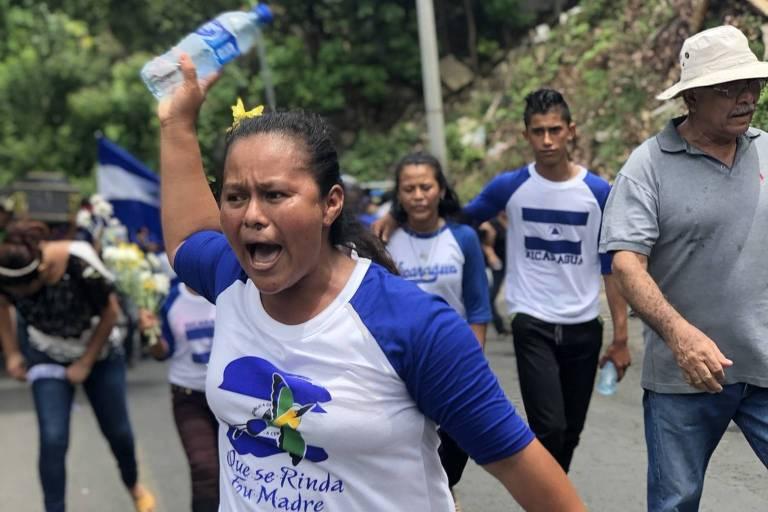 """López aparece gritando na imagem,  com uma garrafa de água na mão. Ela veste uma camiseta com mangas azuis escuras e torso branco, com a mensagem """"Que se renda sua mãe""""."""
