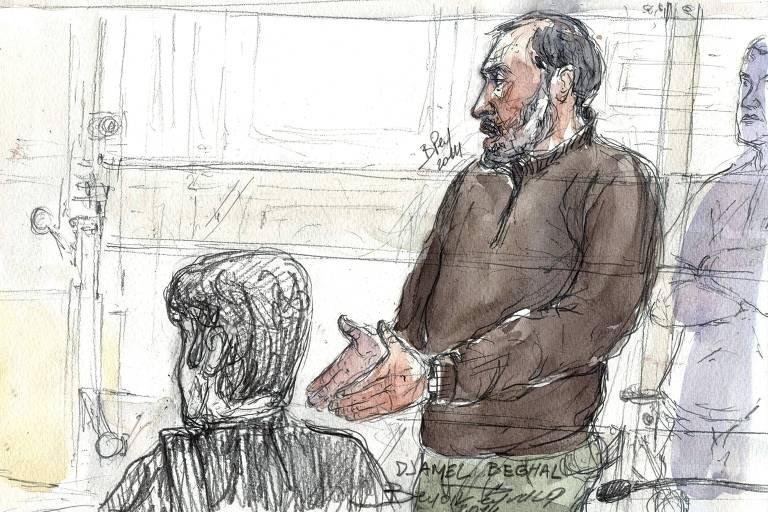 Homem com cabelo com entradas e barba grisalha aparece de pé com casaco preto, calça verde e algemas nas mãos. À esquerda um outro homem com roupa preta está sentado de costas.