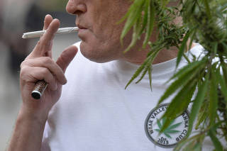 FILE PHOTO: A man prepares to smoke a cannabis cigarette at a legalise cannabis tea party outside the Houses of Parliament, in London